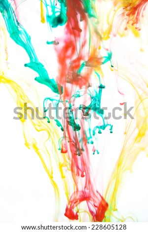 Red and green liquid in water making abstract forms