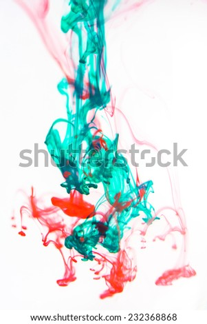 Red and green liquid in water making abstract forms  - stock photo