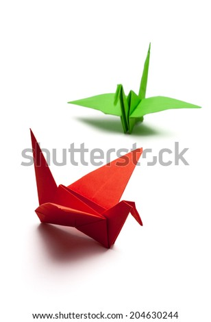 red and green origami paper crane on white paper - stock photo