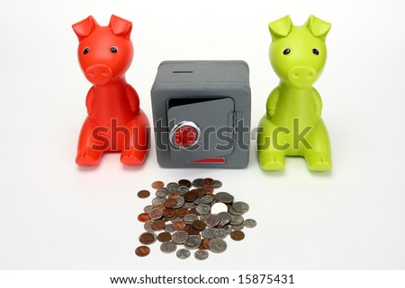Red and Green Piggy banks guarding a combination safe. - stock photo