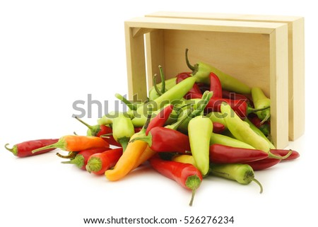 red and green rawit peppers (Capsicum annuum 'Bird's Eye') in a wooden box on a white background