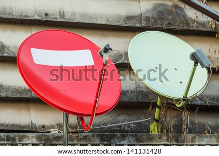 Red and green satellite dishes installed on old building - stock photo