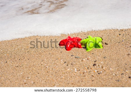 Red and green starfish-shaped molds on the sand with wave - stock photo