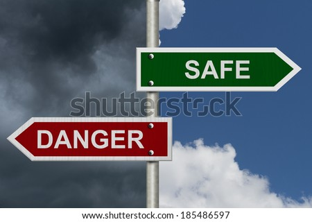 Red and green street signs with blue and stormy sky with words Safe and Danger, Safe versus Danger
