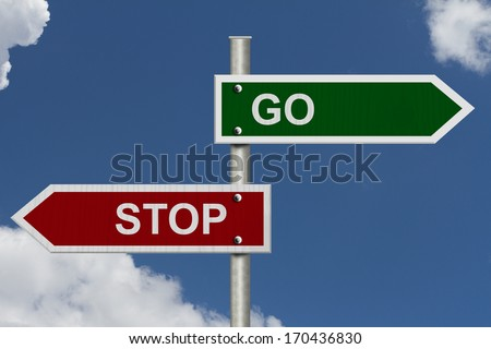 Red and green street signs with blue sky with words Stop and Go, Stop versus Go - stock photo