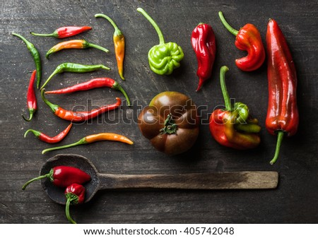 Red and green vegetables and rustic old spoon on dark wooden background, top view. Peppers, chilies and kumato tomatoes - stock photo