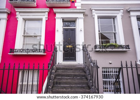 Red and grey painted typical colorful brick houses of Notting Hill district near Portobello road - London, UK - stock photo