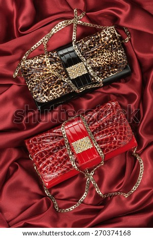 Red and leopard bag  lying on red  fabric, can use as background - stock photo