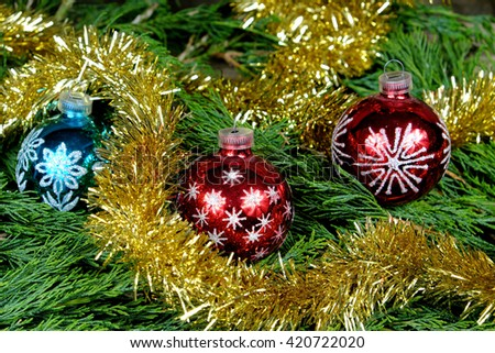 Red and one blue Christmas balls with silver stars around them christmas chain in gold color on old wooden table with green needles - stock photo