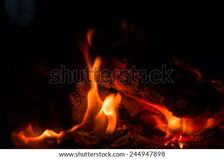 Red and orange flames from burning coal and wood in the fireplace, unfocused - stock photo