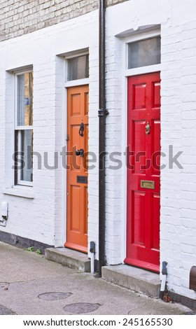 Red and orange front doors on adjoining terraced homes in the UK