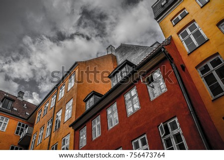 Red and orange houses on a background of black and white sky. Geometry. Copenhagen, Denmark.