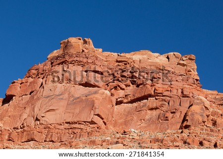 Red and orange rocks of a high cliff offer stark contrast to an brilliant blue sky in the Arizona Desert. - stock photo