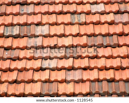 Red and orange roof tiles on an Italian residential building in a small town. Ceramic slate roof.