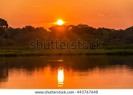 Red and orange sunset over a lake in Madidi National Park in Bolivia - stock photo