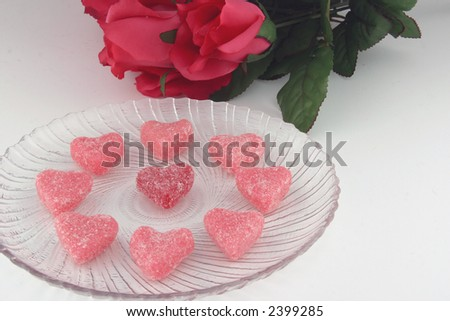 Red and pink heart shaped candy on a fancy clear glass dish with roses in the background.