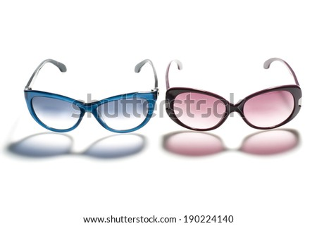 red and pink sunglasses on white background with long shadow - stock photo