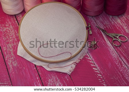 Red and pink threads for sewing and embroidery, fabric in the wooden embroidery hoop