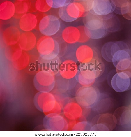 red and purple bokeh christmas lights on dark abstract background