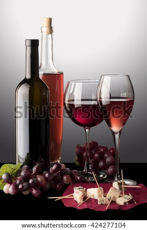 Red and rose wine glasses, bottle of red wine, bottle of rose wine, vine and cheese  - stock photo