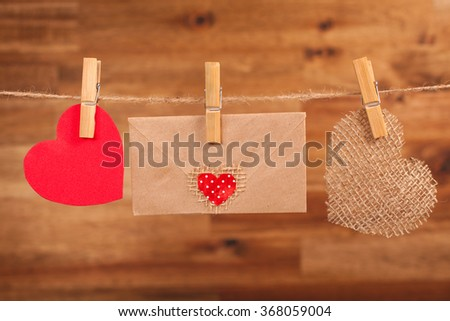 Red and sackcloth hearts,rustic craft envelope hanging on line on wooden background. Valentines day decoration. - stock photo