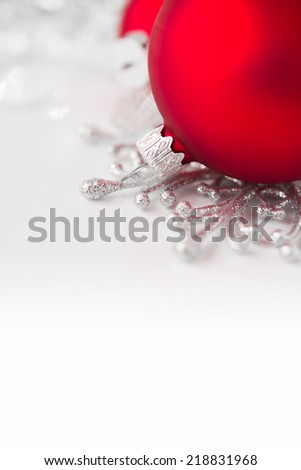 Red and silver xmas ornaments on bright holiday background with space for text - stock photo