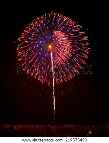 Red and violet fireworks in dark sky background and house light in a far, Malta fireworks festival, 4 July, Independence,explode, fireworks on 15 go August in Zurieq in dark sky background, festival - stock photo