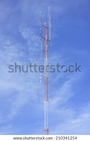 Red and white antenna on blue sky - stock photo