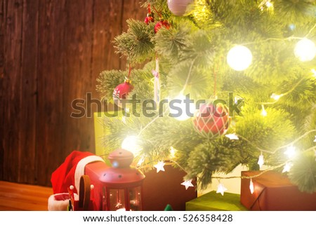 Red and white baubles hanging from a decorated Christmas tree. Christmas background.