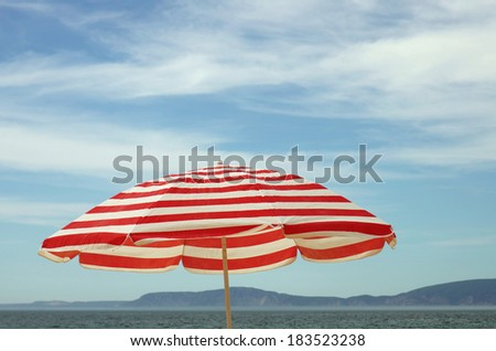 Red and white beach umbrella over blue sky - stock photo