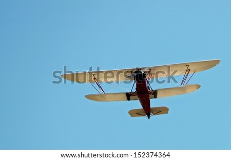 Red and White Biplane Flying in a Blue Sky - stock photo