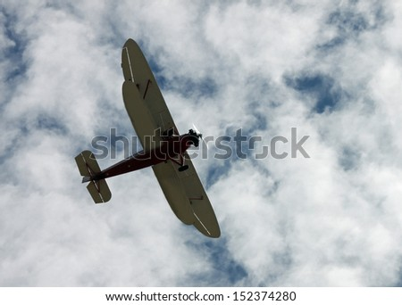 Red and White Biplane in a Blue and White Sky - stock photo