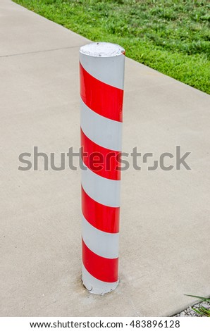 Red and white candy cane striped concrete barrier post in Santa Claus, Indiana where it is Christmas all year long