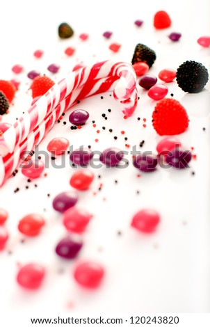 red and white candy cane with multiple candies on a white background