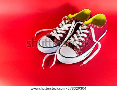 Red and white canvas style sneakers on a red background - stock photo