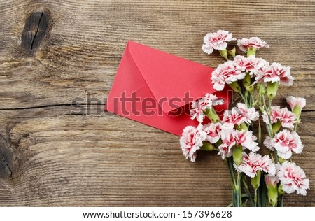 Red and white carnations and red envelope isolated on wooden background. Copy space - stock photo