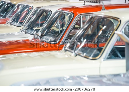 Red and white cars in a row on parking lot  - stock photo