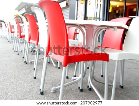 Red and white chairs with tables in an outdoor bar on the road