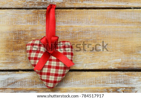 Red and white checkered heart on red ribbon on rustic wooden surface with copy space