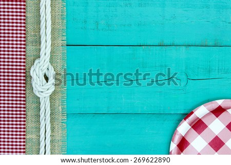 Red and white checkered plate on antique teal blue wood sign with gingham, rope and burlap border; above view looking down - stock photo