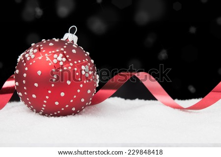 Red and white Christmas ball and ribbon on a black background - stock photo