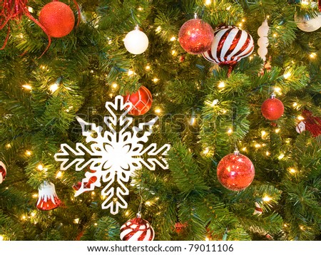 Red and White Christmas Ornaments on a Green Tree with White Lights - stock photo