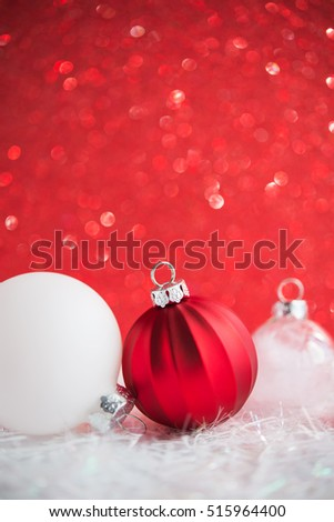 Red and white christmas ornaments on red glitter bokeh background. Merry christmas card. Winter holiday xmas theme. Happy New Year. Space for text.