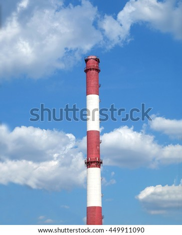 Red and white colored stripe industrial smoke pipe on blue sky with white clouds vertical photo