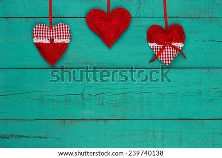 Red and white country fabric hearts hanging on antique teal blue wooden background - stock photo