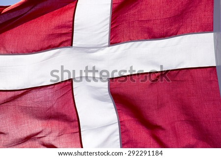 Red and white Danish flag blowing in the wind. - stock photo