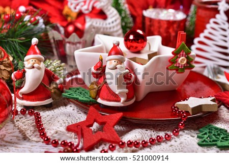red and white decoration of christmas table with star shaped bowl and santa figurine