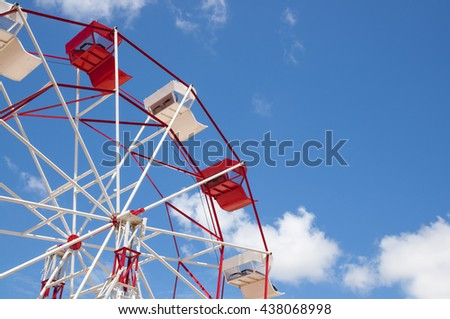 Red and white ferris wheel against a sky background - stock photo