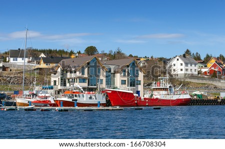 Red and white fishing boats stand moored in Norway village - stock photo