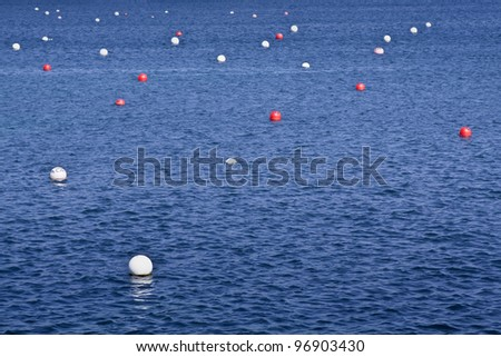 Red and white floats in the bay of Cadaques, Girona, Spain - stock photo